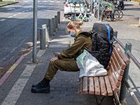 חיילת יושבת בתחנת אוטובוס / צילום: כדיה לוי, גלובס