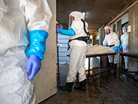 עובדי חברת קדישא ממוגנים מובילים גופה של אדם שנפטר מקורונה / צילום: Oded Balilty, Associated Press