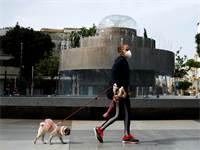אישה שעוטה מסכה מטיילת עם הכלבה שלה בכיכר דיזינגוף בתל אביב / צילום: Corinna Kern, רויטרס