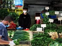 מוכר עוטה מסכה בשוק הכרמל בתל אביב. השוק נפתח מחדש עם ההקלה במגבלות  / צילום: Amir Cohen, רויטרס