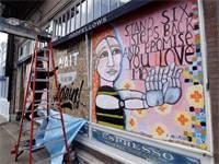 """אמן מצייר על לוחות שחוסמים מסעדות סגורות בסיטאל, ארה""""ב / צילום: Elaine Thompson, AP"""