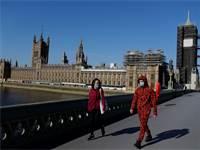 אנשים עם מסכות הולכים על רקע בניין הפרלמנט הבריטי בלונדון / צילום: Kirsty Wigglesworth, AP