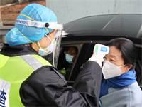 איש ביטחון בכביש אגרה בסין בודק את חום גופה של נוסעת, כדי לשלול הידבקות בנגיף קורונה / צילום: Martin Pollard, רויטרס