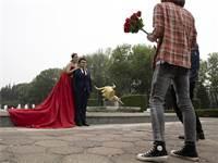 זוג סיני מצטלם לתמונות חתונה בפארק העולמי בבייג'ינג / צילום: Ng Han Guan, Associated Press