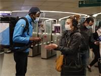 עובד ברכבת התחתית בפריז נותן ג'ל לחיטוי ידיים לנוסעת / צילום: Francois Mori, AP