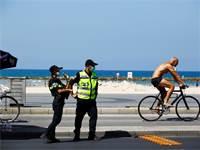 שוטרים בחוף הים בתל אביב לפני כניסת יום הכיפורים / צילום: Corinna Kern, רויטרס