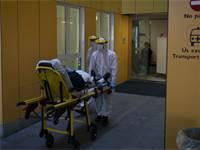 פרמדיקים מעבירים חולה קורונה לאמבולנס בספרד / צילום: Felipe Dana, AP