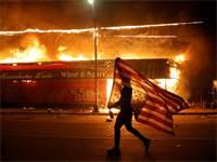 """מפגין נושא את דגל ארה""""ב הפוך ליד בניין בוער במינאפוליס, העיר שבה נרצח ג'ורג פלויד / צילום: Julio Cortez, AP"""