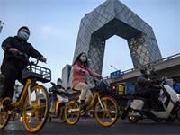 אנשים עם מסכות נוסעים ברחובות ביג'ינג, סין / צילום: Mark Schiefelbein, AP