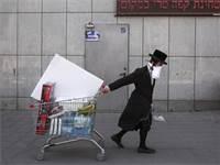 חרדי תושב בני ברק עם מסכת פנים סוחב עגלת קניות  / צילום: Oded Balilty, AP