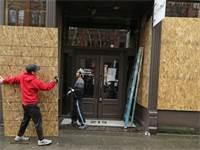 מסעדה סגורה בסיאטל. בעל המסעדה חוסם את החלונות כדי למנוע ביזה / צילום: Ted S. Warren, AP
