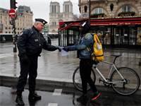 שוטר צרפתי בודק את מסמכיו של אדם שיצא מביתו בפריז / צילום: Francois Mori, AP