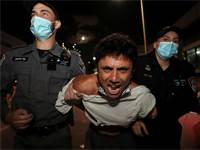 """שוטרים עוצרים מפגין בת""""א. מפגינים בכל הארץ יצאו במחאה על הניסיון להגביל את ההפגנות נגד ראש הממשלה / צילום: Ammar Awad, רויטרס"""