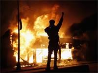 מפגין מול בית עסק להחלפת צ'קים שעולה באש ביום שישי במינאפוליס, העיר שבה נרצח ג'ורג' פלויד בן ה-46  / צילום: John Minchillo, AP