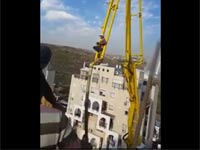 עובד בניין תלוי על מנוף/ צילום: מתוך הוידאו