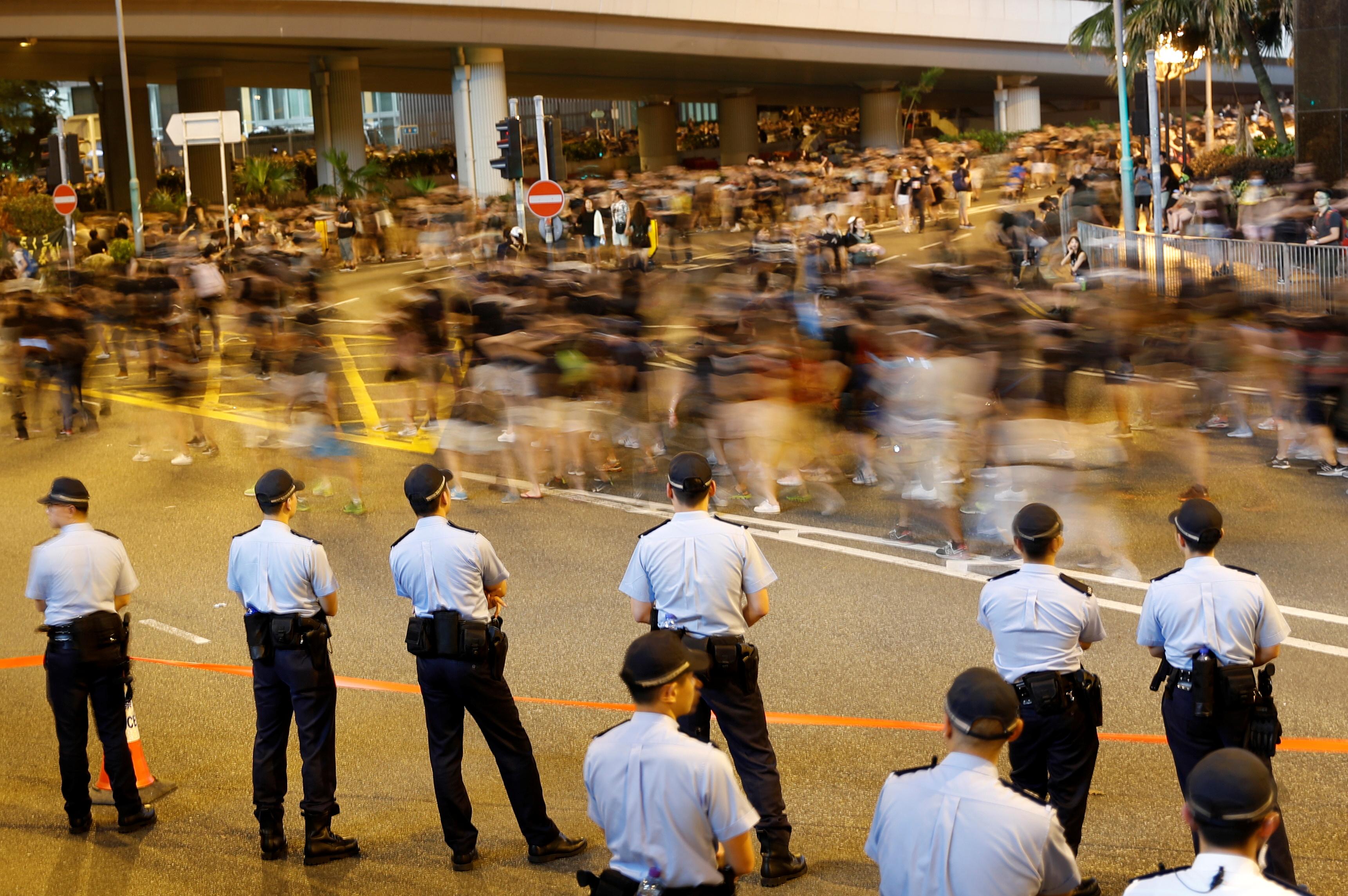 שוטרים שומרים בעד שמפגינים נגד מנהיגת הונג קונג צועדים / צילום: Tyrone Siu, רויטרס