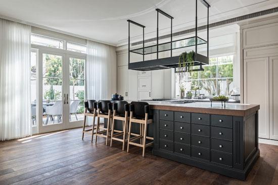 במרכז המטבח אי גדול מכוסה בפלטת עץ אלון גושני, ומעליו קולט אדים שמשמש גם כאלמנט עיצובי / צילום: שי אדם, גלובס