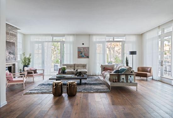 בסלון מערכת ישיבה מקטיפה שמוטמע בה מדף דקורטיב וכן יצירות אמנות ואלמנטים אקלקטיים / צילום: שי אדם, גלובס