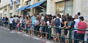 """מהגרי עבודה מחכים בתור לכניסה ללשכת האוכלוסין והגירה בת""""א / צילום: תמר מצפי"""