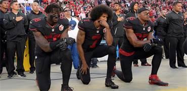 שחקני הפוטבול קולין קפרניק (במרכז), אלי הרולד ואריק ריד כורעים ברך בהשמעת ההמנון האמריקאי \ צילום: ר