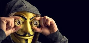 האקר במסיכת אנונימוס מחזיק בביטקוין / צילום: shutterstock
