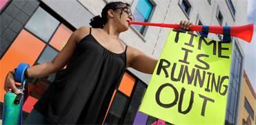 """מפגינה סביבתית נושאת שלט: """"הזמן אוזל"""" / צילום: ומ. גאלשין, רויטרס"""