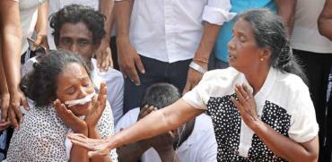 אישה בטקס קבורה המוני יומיים אחרי סדרת הפיגועים בסרי לנקה/ צילום:  רויטרס