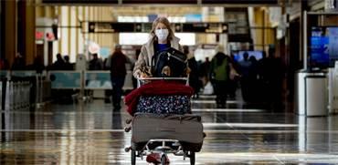 """אישה עם מסכה בנמל התעופה רונלד רייגן בוושינגטון, ארה""""ב / צילום: Andrew Harnik, AP"""