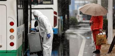 עובד בחליפת מגן עוזר להוביל מזוודה לאוטובוס / צילום: צ'יינה דיילי, רויטרס