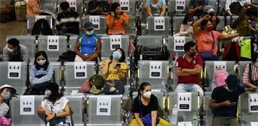 שמירה על מרחק זה מזה בישיבה בתחנת אוטובוס בתאילנד / צילום: Challinee Thirasupa, רויטרס