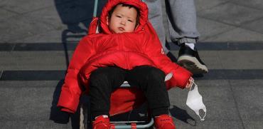 פעוט בבייג'ין מחזיק בידו במסכת המגן שלו / צילום: Andy Wong, Associated Press
