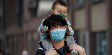 משפחה ברחובות בייג'ין הולכת ממוגנת מחשש להדבקות / צילום: Associated Press