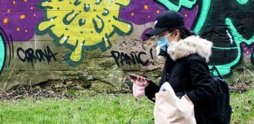 עוברת אורח מסתכלת בנייד כשברקע גרפיטי בבריטניה על ההסטריה בצל הקורונה / צילום: Massimo Paolone/LaPresse, Associated Press
