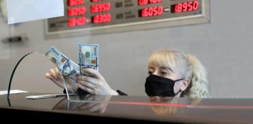 עובדת דלפק בדוכן להמרות מטבע ממירה לשטרות דולרים / צילום: Burhan Ozbilici, Associated Press