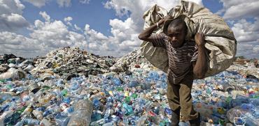אזרח קניה נושא שק של פלסטיק למחזור בשכונת העוני דנדורה בניירובי  / צילום: Ben Curtis, Associated Press