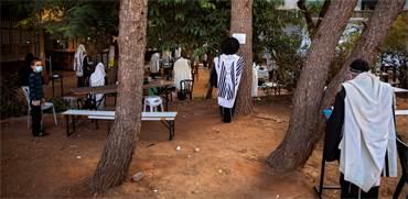 מתפללים מחוץ לבית הכנסת בבני ברק / צילום: Oded Balilty, AP