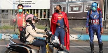 שוטרים בתלבושות גיבורי על מרססים חומר חיטוי על נהגים במהלך קמפיין מודעות לנגיף הקורונה באינדונזיה / צילום: AP
