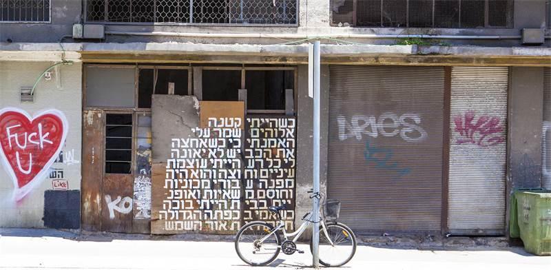 משוררת הרחוב ניצן מינץ מפרסמת את שיריה על קירות הרחוב / צילום: שחף דקל