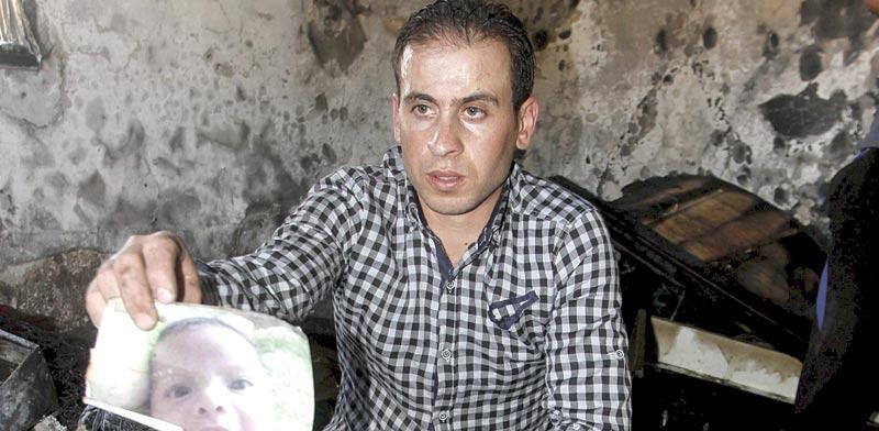 קרוב משפחה של התינוק עלי דוואבשה מציג את תמונתו בזירת הרצח / צילום: רויטרס
