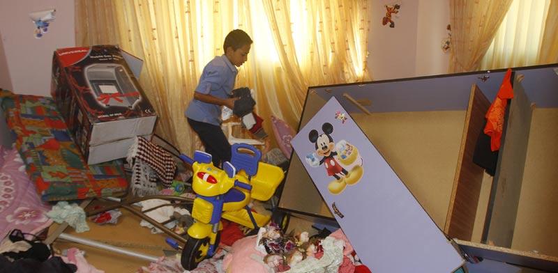ילד פלסטיני בוחן את חדרו לאחר שלטענת המשפחה כוחות הביטחון ערכו חיפוש  בביתם/צילום: רויטרס