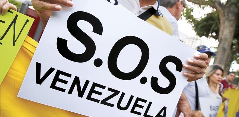 מפגין מוחה נגד משטרו של נשיא ונצואלה מאדורו / צילום: רויטרס