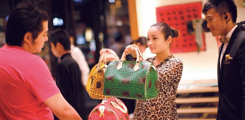 קונה בחנות של לואי ויטון בשנחאי / צילום: רויטרס