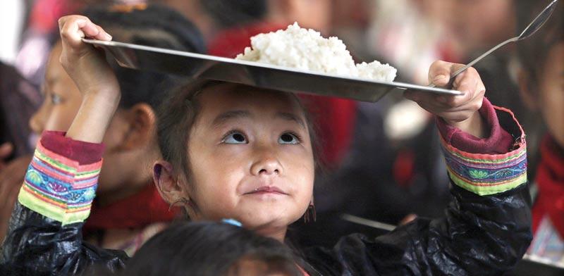 ילד סיני ועל ראשו קערת אורז / צילום: רויטרס