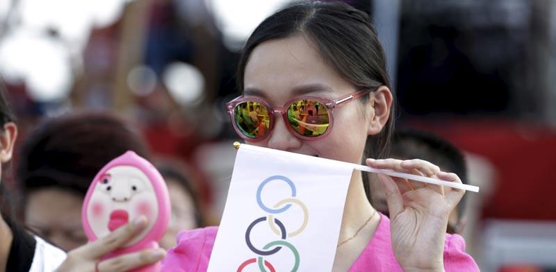 אישה סינית עושה סלפי עם דגל של הטבעות האולימפיות / צלם: רויטרס