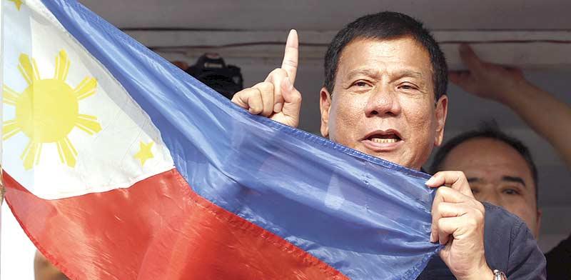 רודריגו דוטרטה ודגל הפיליפינים. המסרים הקיצוניים נופלים על אוזניים כרויות בציבור / צילום: רויטרס