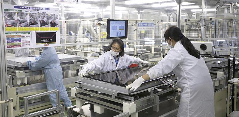 פועלות מרכיבות מסך LCD במפעל של שארפ / צילום:בלומברג