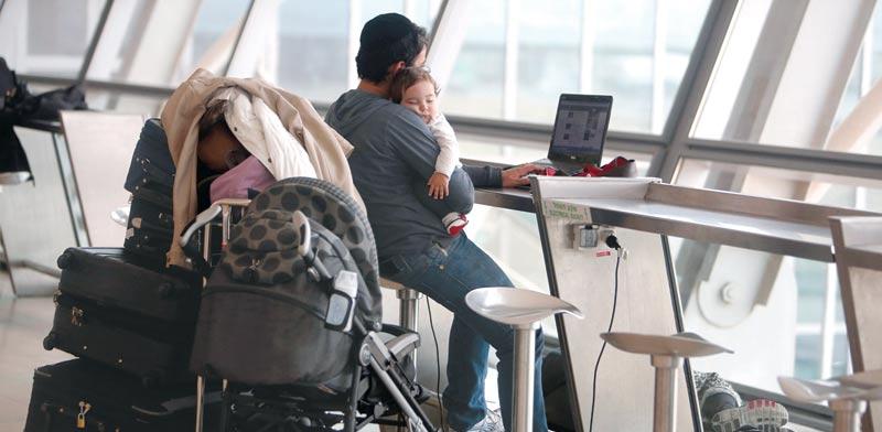 עובד מפעיל לפטופ בשדה תעופה ותינוקו על ידיו / צילום: רויטרס