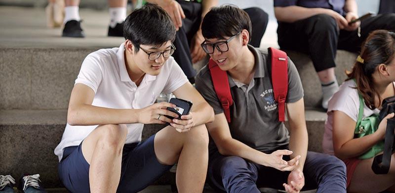 צעירים משתמשים בטלפון נייד / צילום: בלומברג
