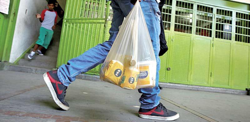 אדם מחזיק שקית ניילון / צילום: בלומברג