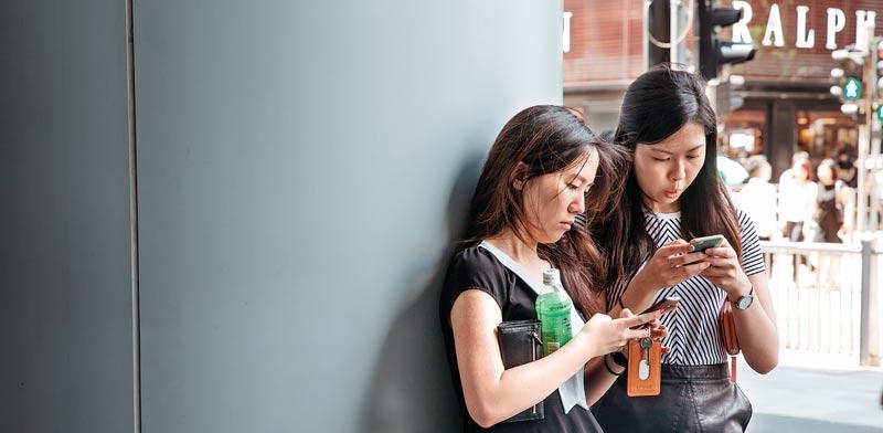 בחורות סיניות מרותקות לסמארטפון / צילום: בלומברג